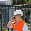 Engineer with phone near the electricity substation — Stock Photo