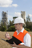 Engineer with folder near the factory — Stock Photo