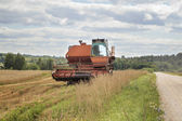 Old harvester on the field near road — Stock Photo