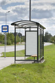 Bus stop with the ad in suburb — Stock Photo