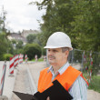 Royalty-Free Stock Photo: Engineer with a folder near the sidewalk repairing
