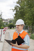 Engineer with a folder near the sidewalk repairing — Stock Photo