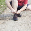 Stock Photo: Man tied shoe laces on the trail front view