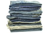 Jeans stacked together on a white background — Stockfoto