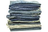 Jeans zusammen gestapelt auf weißem hintergrund — Stockfoto