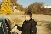 Someone from the car is offering money to the boy — Stock Photo