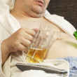Stock Photo: Drunk masleep with beer in hands of