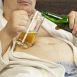 Man sitting on the couch with a beer in the hands of — Stock Photo