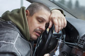 Drunk man lying on the steering wheel — Stockfoto