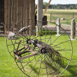 Stock Photo: Old, rusty farm machinery hay rake near farm