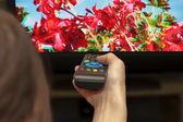 Remote control in hand against 3D TV screen — Stock Photo