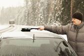 Man cleans the car out of the snow in snow storm — Stockfoto