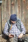 Homeless leaning against barn door — Stock Photo