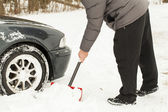 Man digging car out of the snow — Stock Photo