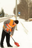 Man with a snow shovel clean the sidewalk — Stock Photo