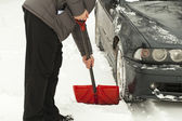 Man with shovel clears snow around the car — Stock Photo