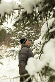 Man looking for a Christmas tree in the woods — Stock Photo