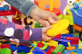 The mother and the child's arms at the toy pile — Stock Photo
