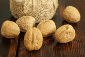 Walnuts placed on an old table in dark brown color — Stock Photo