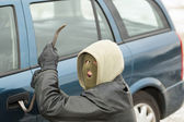 Robber with a crowbar near the car door — Stock Photo