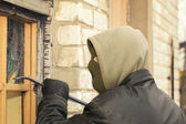 Robber with a crowbar crashed warehouse window — Stock Photo