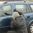 Stock Photo: Robber with crowbar trying to open car door