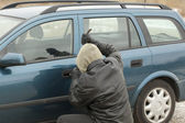 Robber with a crowbar trying to open the car door — Stock Photo