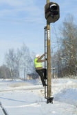 Railroad worker climbing on signal beacons pole — Stock Photo