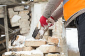 Worker throws bricks near the burned old house — Stock Photo