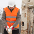 Worker with brick in hands on burned house background — Stock Photo