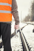 Worker with adjustable wrench in the hands on railway crossings — Stock Photo