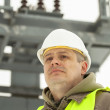 Engineer on a transformer background in winter — Stock Photo #20699803
