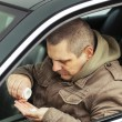 Stock Photo: Msitting in car with drugs in hands