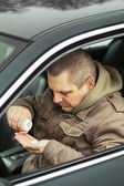 Man sitting in car with drugs in the hands — Stock Photo