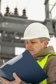 Engineer with folder on a transformer background — Stock Photo