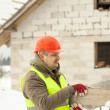 Builder with board at the hands near the construction works — Stock Photo