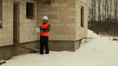 Safety inspector worker talking on the phone near new building — Stock Video