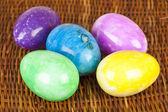 Huevos de pascua en diferentes colores en la superficie trenzada — Foto de Stock