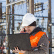 Stock Photo: Electrical engineer with computer near electricity substation