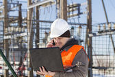 Electrical engineer with computer near the electricity substation — Stock Photo