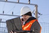 Elektricien met pc en mobiele telefoon in de buurt van het onderstation elektriciteit — Stockfoto