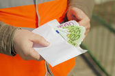 Employee's hands with euro banknotes in envelope — Stock Photo
