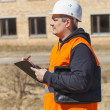 Stock Photo: Building inspector with folder near abandoned house