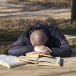 Student lying asleep on books outside on a bench - Stock Photo