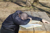 Man lying asleep on books outside on a bench — Stock Photo