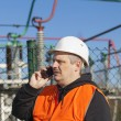Electrical engineer talking on the phone at the electric substation — Stock Photo