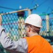 Electrical engineer touched a hand to the fence at the electric substation — Stock Photo