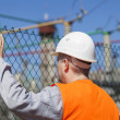 Electrical engineer touched a hand to the fence — Stock Photo
