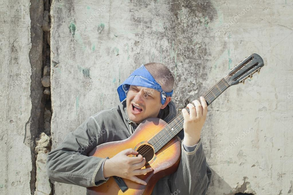 Man Playing Guitar Leaning Against Wall Stock Photo