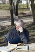 Tired man reading a book outdoors on a bench — Stock Photo